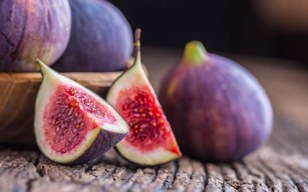 Figs. A few figs in a bowl on an old wooden background.